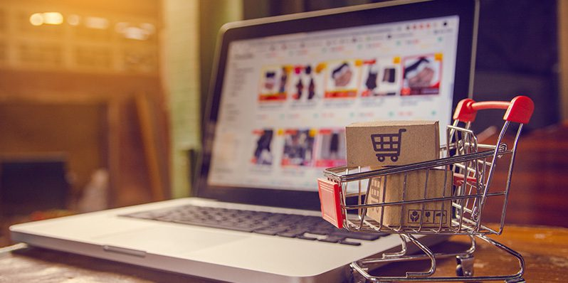 Image of laptop on desk next to miniature shopping cart
